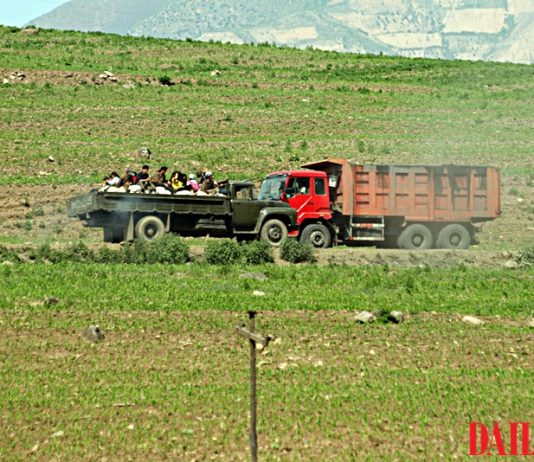 A truck transporting coal and a servi-cha transporting people from Musan Mine in North Korea
