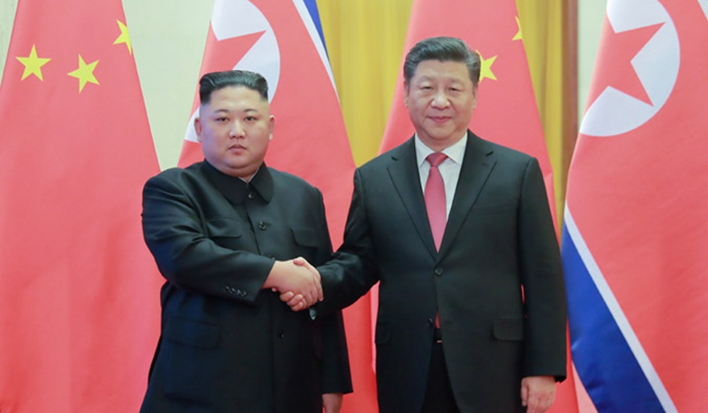 Kim Jong Un and Xi Jinping shake hands during Kim Jong Un's fourth visit to China in January 2019