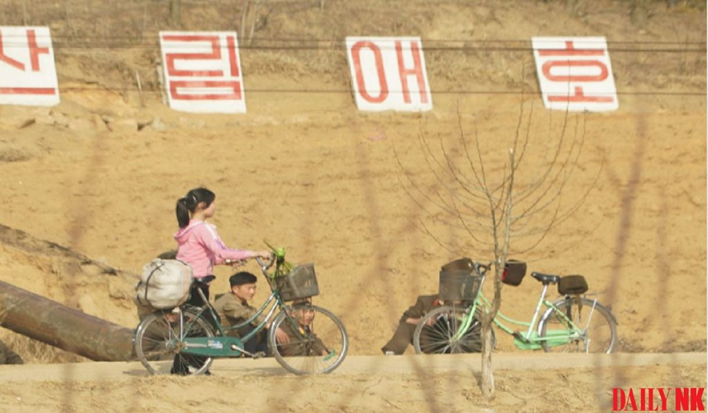 A woman in Wonsan, Kangwon Province rides her bike past propaganda signage promoting forest protectio