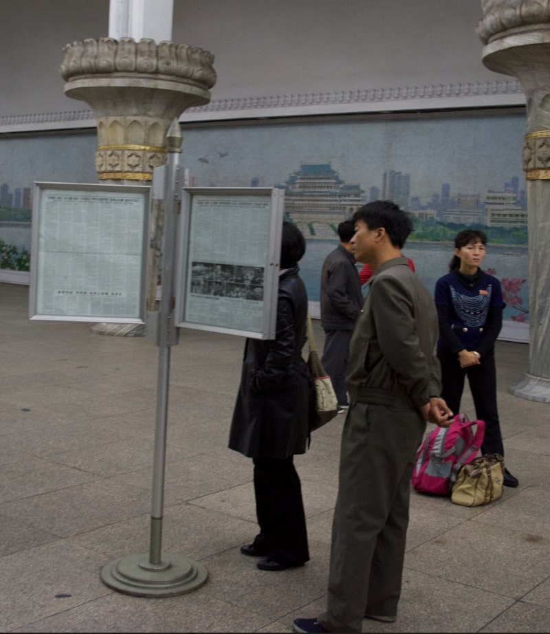 North Koreans in Pyongyang reading the Rodong Sinmun in a subway station
