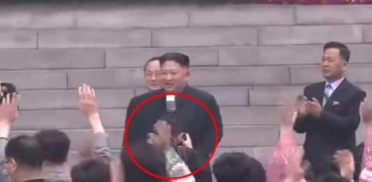 Ri, circle in red, photographing Kim Jong Un on March 10 during the Supreme People's Assembly elections
