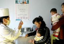 A medic administers a vaccination to a child in North Korea