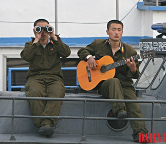 North Korean soldiers on a boat in Sinuiju, North Pyongan Province