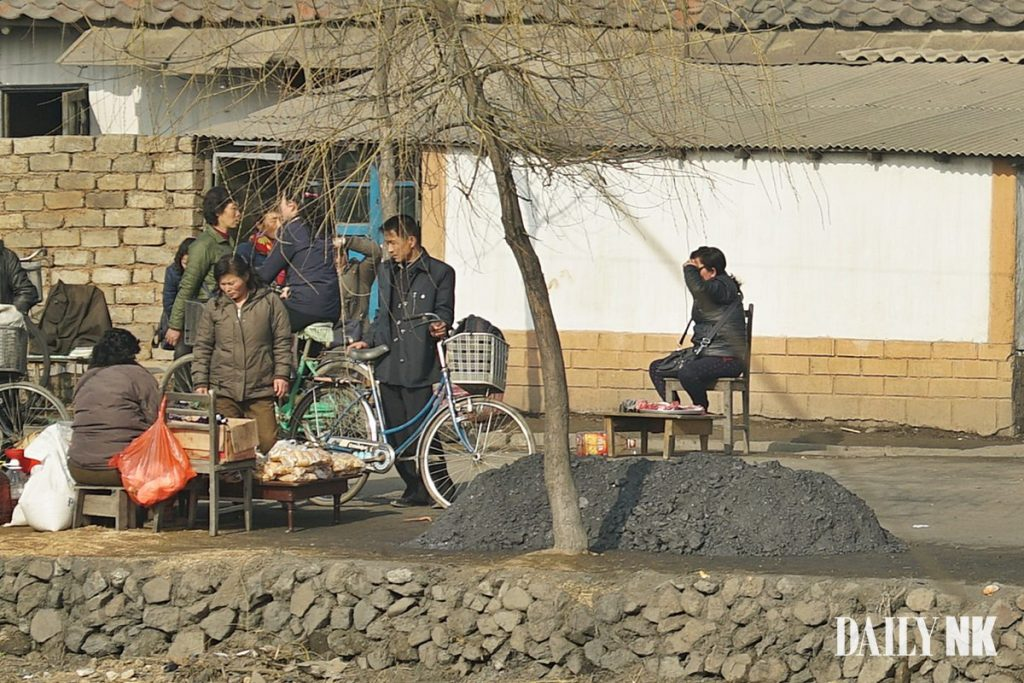 Coal dust piled up next to street merchants in Sunchon, South Pyongan Province in this photo taken in October 2018