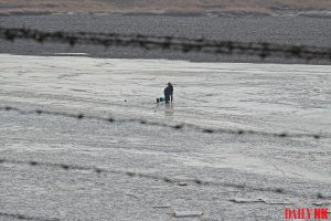 A North Korean resident in Onsong County, North Hamgyong Province draws water from the frozen river in March 2019