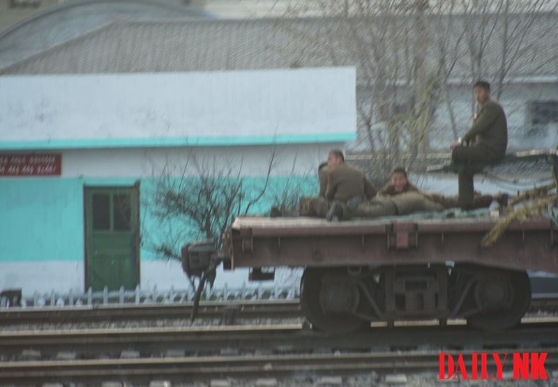 North Korean soldiers head to a construction site on a cargo train