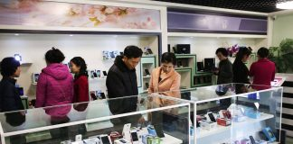 North Koreans peruse cell phones on offer