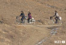 North Korean women bikes support